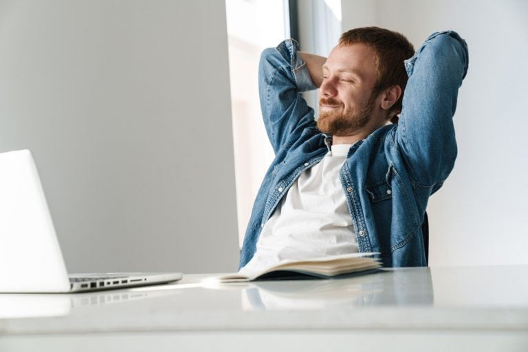 Photo of happy man smiling and resting while working with laptop