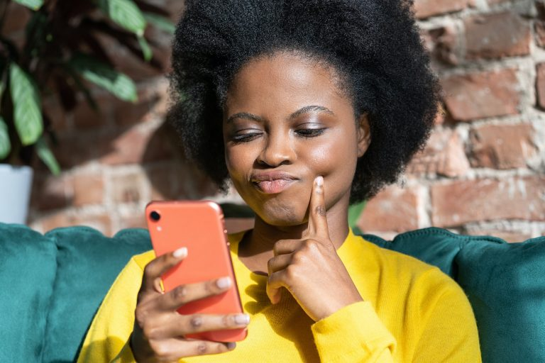 Black woman ponders on how to answer question, using mobile phone, tries to made up good message